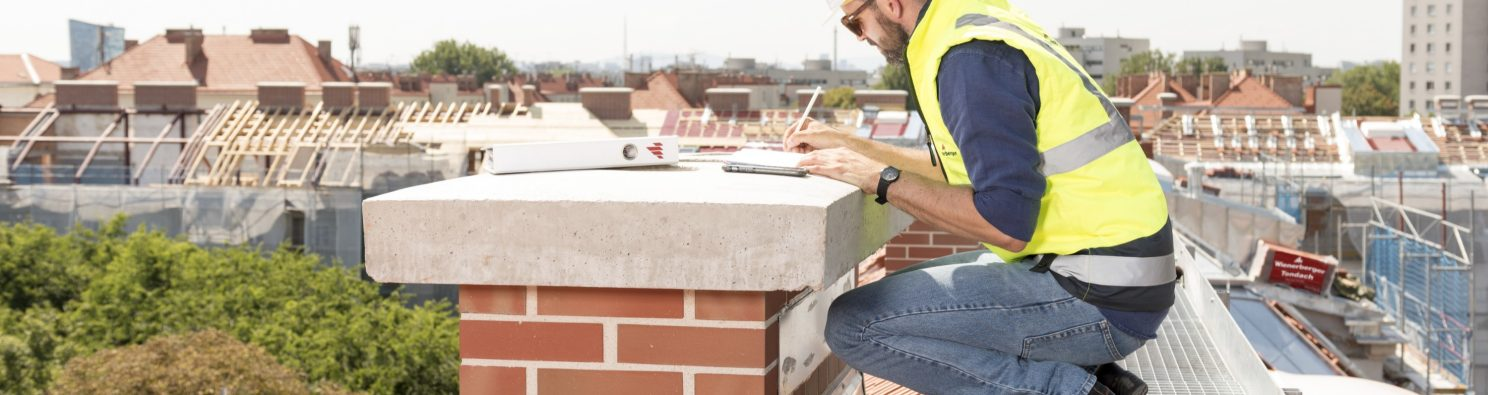 Workers on roof builder checking chimney taking notes