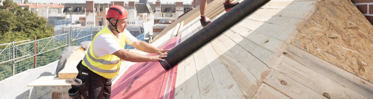 Urban roofers applying roof underlay sheet wearing hard hat and safety jacket brick chimney
