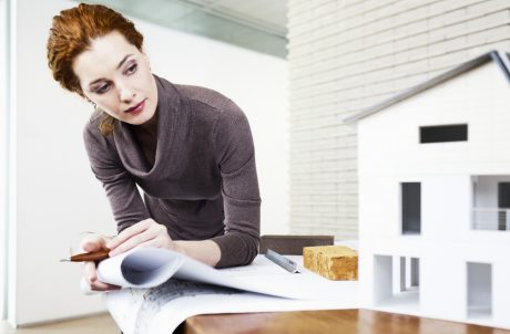 Female planner or architect with blueprint and mock-up of a house at the office